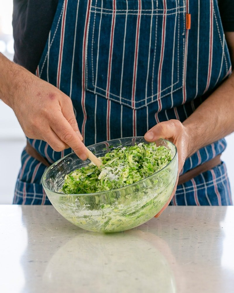 mixing a bowl with a zucchini batter