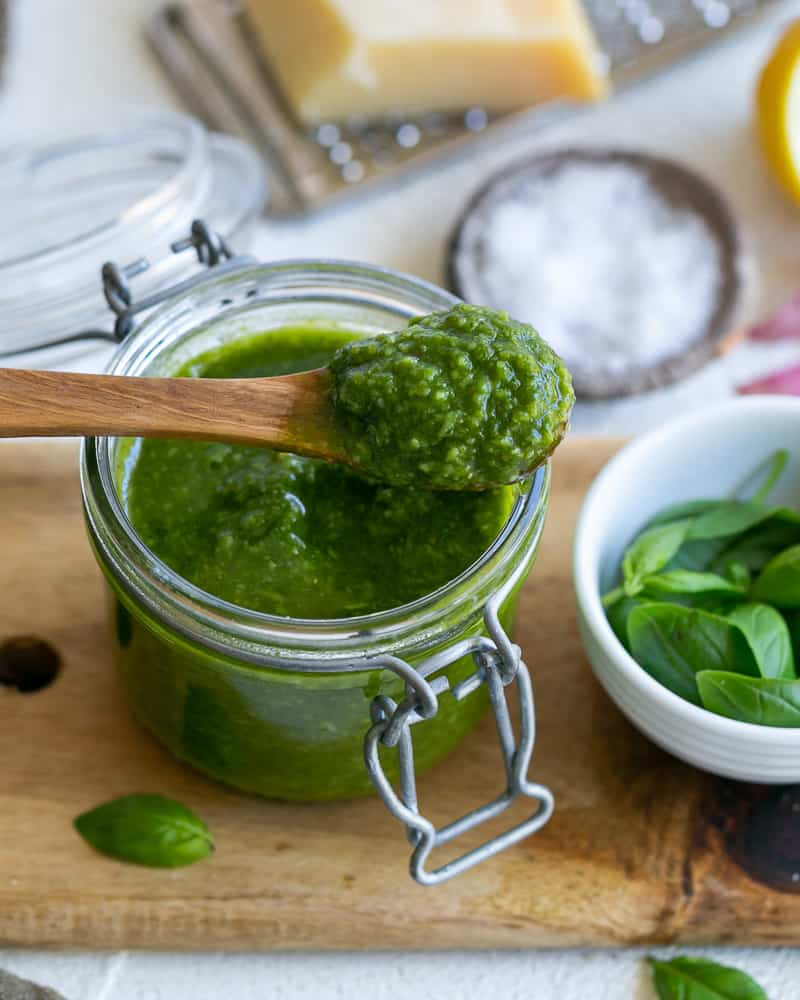 Basil Pesto in a jar with a wooden spoon
