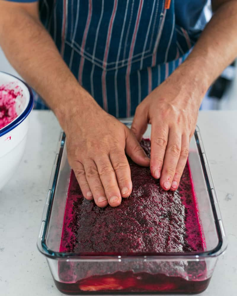 Salmon covered in beet curing mix in a deep glass dish