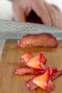 Cured Salmon sliced with sharp knife on a wooden chopping board