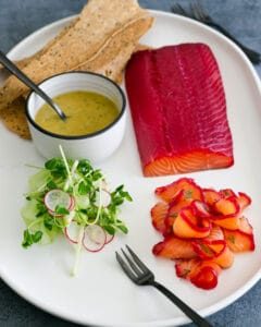 Cucumber Salad, Mustard Dill sauce, Beet cured Salmon and Lavosh cracker on a white platter