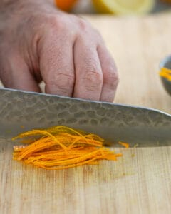 Picture showing how to julienne the orange zest with a sharp knife on a wooden chopping board