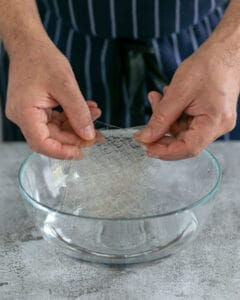 Gelatin sheets being submerged in a bowl of water