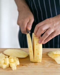 Chopping and dicing peeled pineapple