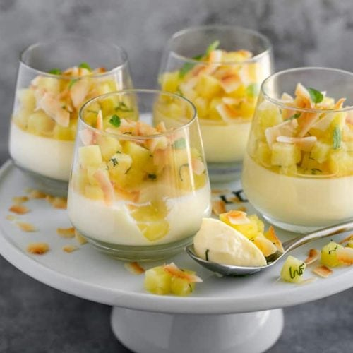 4 dessert glasses on top of a white cake stand with ready to eat pina colada panna cotta