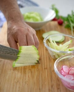 Slicing green apple into thin strips, using a sharp knife