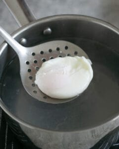 taking out a Poached egg with a slotted spoon from a pot of hot water