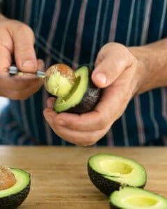 Removing the stone from half cut avocado