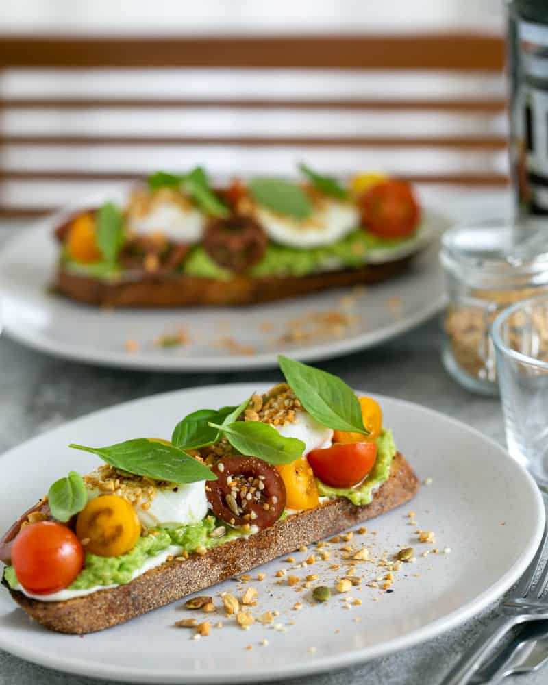 breakfast set up on table with Slice of sourdough with ricotta, crushed avocado, poached eggs, cherry tomatoes, basil and dukkah