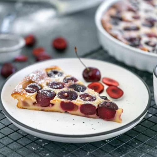 Slice of baked Cherry Clafouti Tart in a plate on a cooling rack