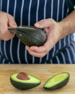 Avocado being cut in two halves