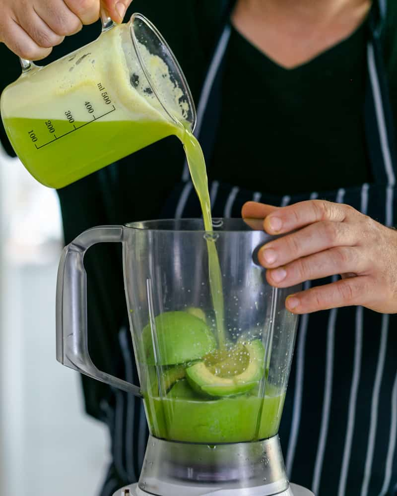 Apple juice mixed with lime juice being poured over avocados in the mixer