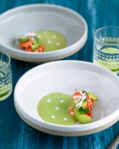 Overhead shot of Avocado soup in a bowl with fresh avocado slices, poached prawns, garnished with coriander and sliced radish