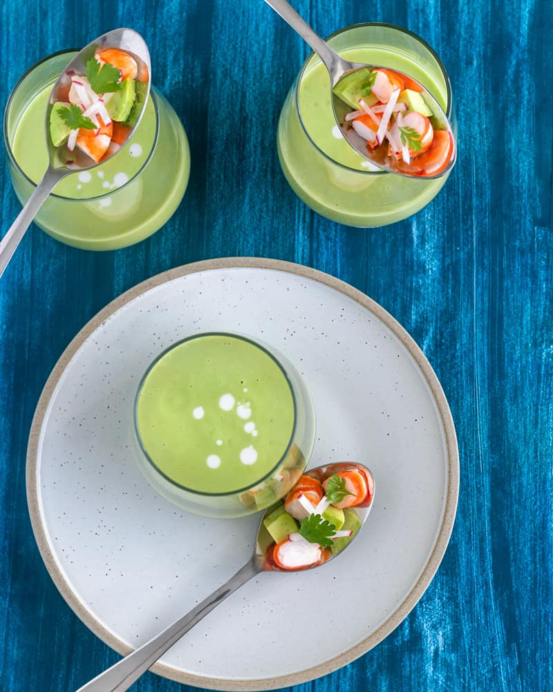 Canape style avocado and green apple soup in a dessert glass with prawn salad on a spoon