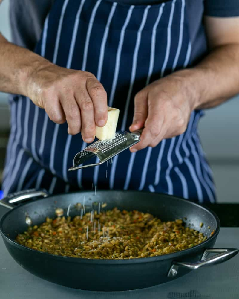 Grating Parmesan on cooked risotto in a pan