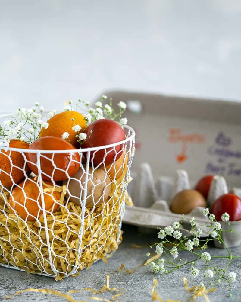 Colourful Easter Eggs in white wire basket