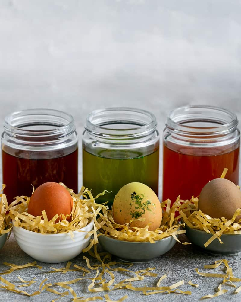 Red and Yellow coloured Easter Egg in front of jars filled with coloured water