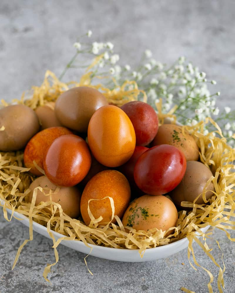 Coloured Easter Eggs brushed with oil and arranged in a white bowl