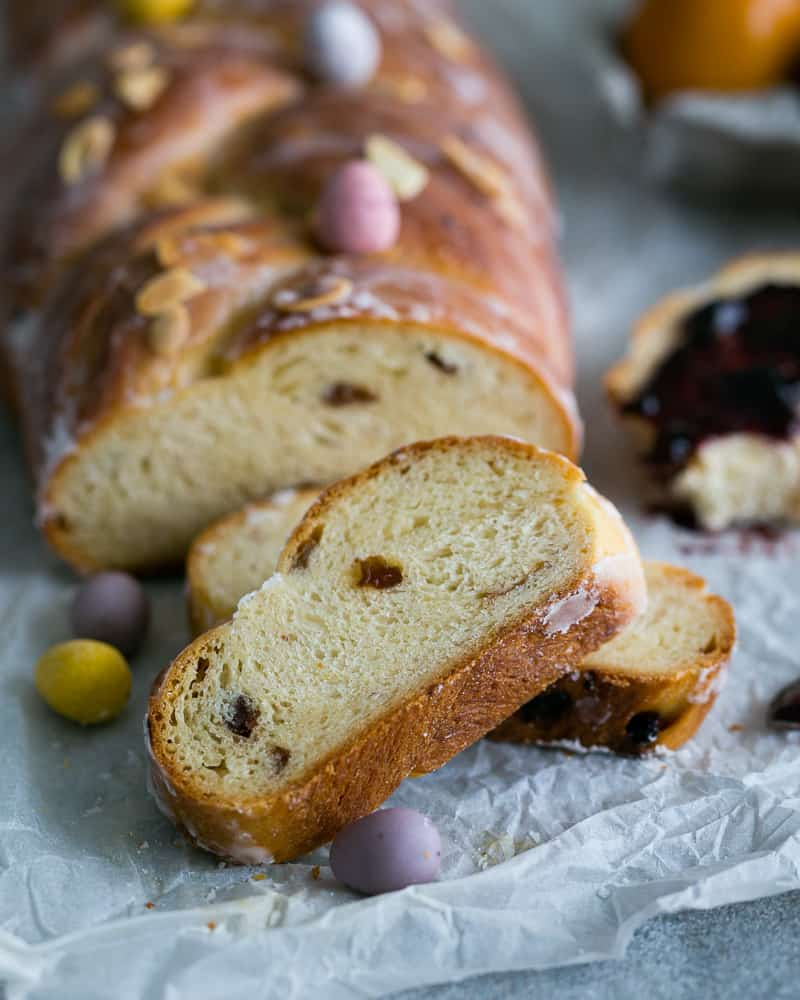 Sliced Easter Zopf with Raisins and Lemon Glaze decorated with small colourful chocolate Easter eggs