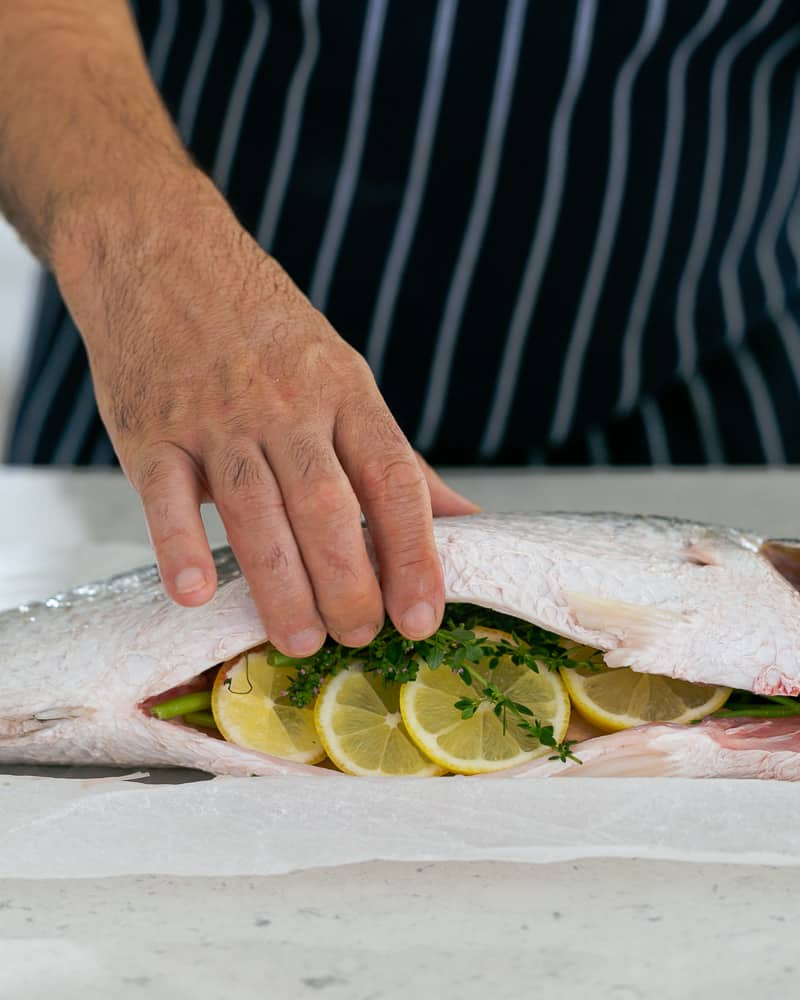 Whole Barramundi stuffed with Herbs and Lemon for salt-baking and served with salsa verde
