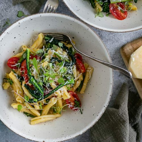 two bowls of Casarecce Pasta with Asparagus, Kale and Garlic with block of parmesan on the side