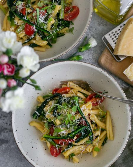 Two bowls of Casarecce Pasta with Asparagus, Kale and Garlic with Parmesan block on grater on a wooden board