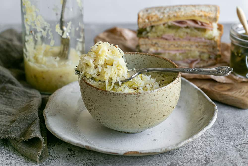 Fermented Sauerkraut served in a ceramic bowl with a fork on top showing a scoop of sauerkraut