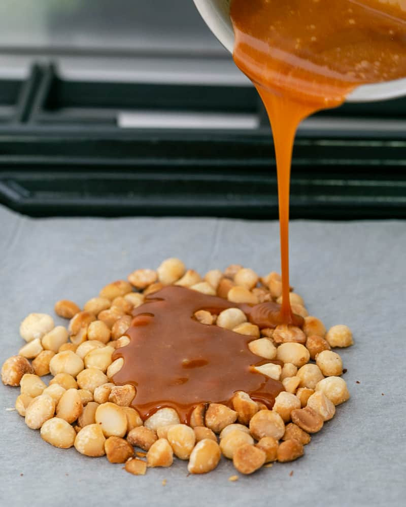 Pouring the hot caramel on the oven roasted macadamia nuts