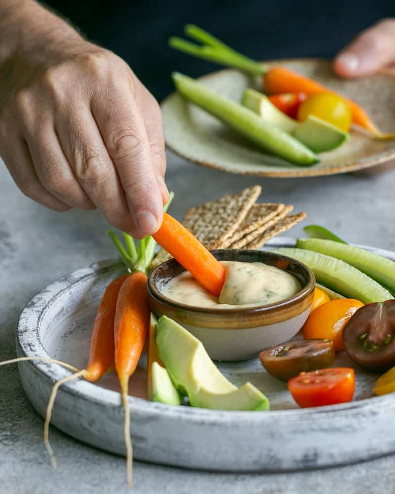 Dipping a baby carrot in the garlic aioli sauce