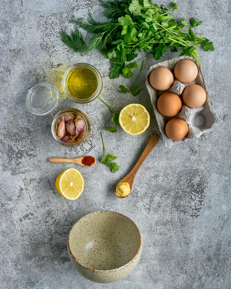 Ingredients for making Confit garlic and herb aioli sauce.  Lemon, mustard. paprika, confit garlic, eggs, fresh herbs like coriander, dill and parsley, grape seed oil