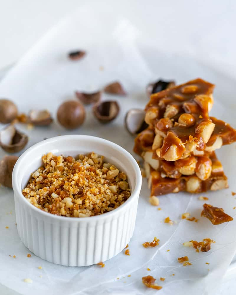 Crispy macadamia nut brittle crumble in a white bowl with a small stack of brittle next to it