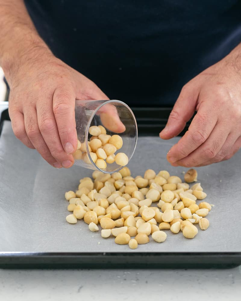 Halved Macadamia nuts spread on baking tray lined with baking paper