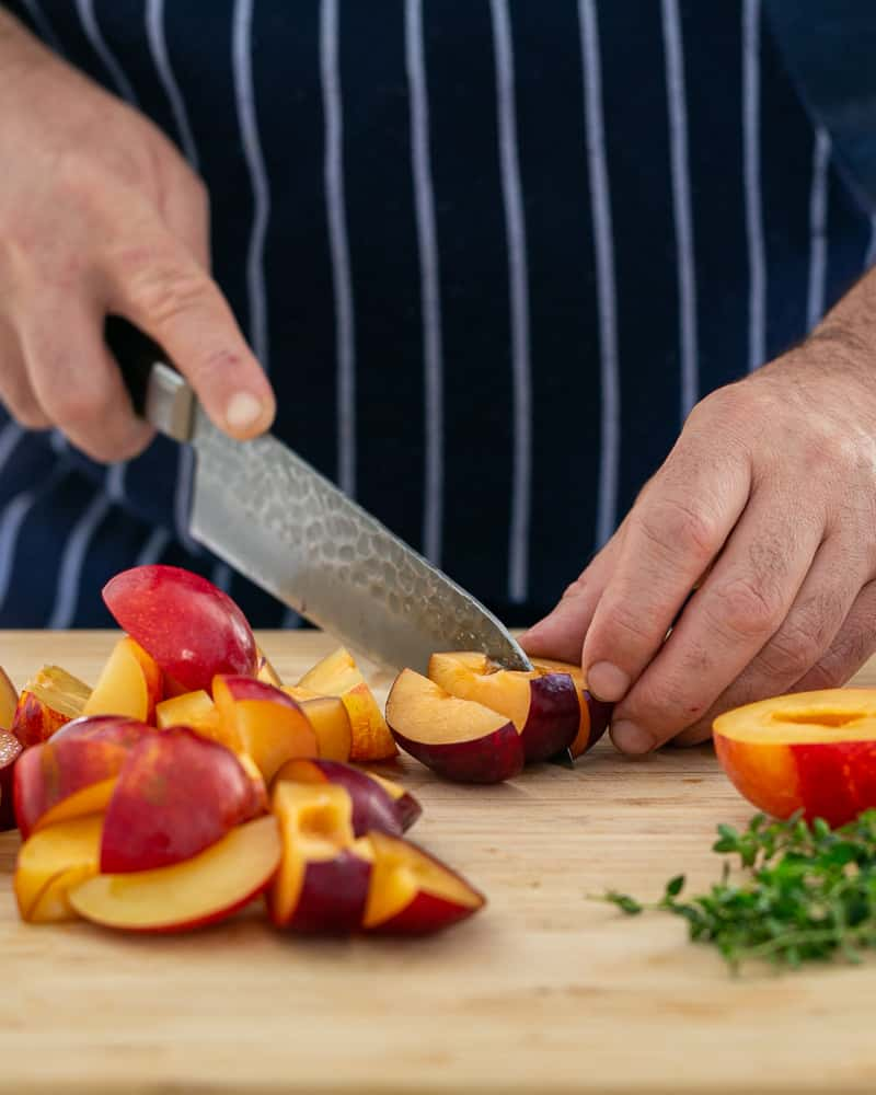 Cutting the halved plums into wedges with a sharp knife on a chopping board