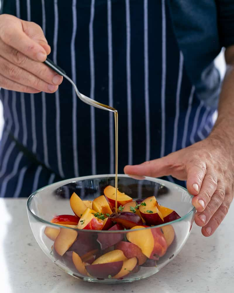 Adding a Teaspoon of vanilla essence to the plum wedges mixed with lemon thyme in the glass bowl for plum tarte tatin