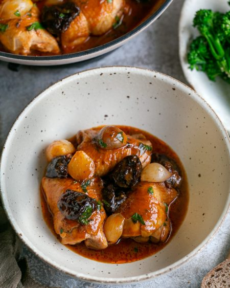 Chicken braised with prunes and shallots served in a bowl with the pan in the background