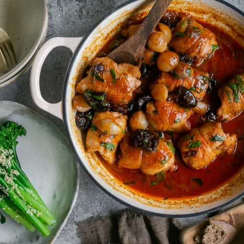 Chicken braised with prunes and shallots in a pan served with a side of broccolini and sourdough bread