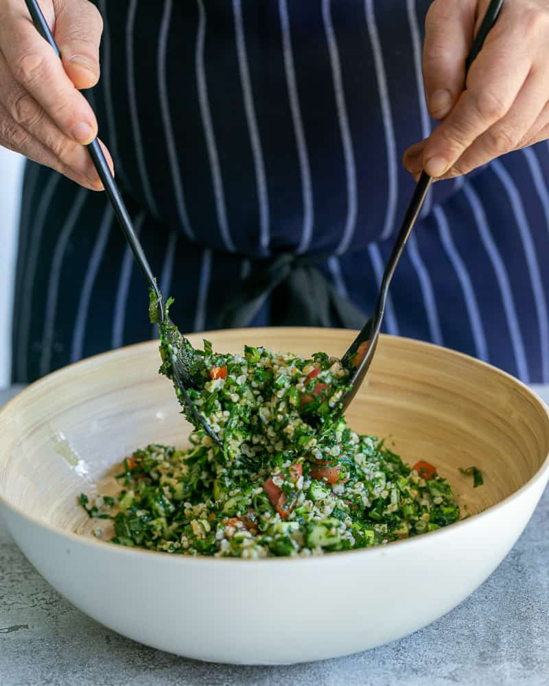 Tossing the tabbouleh salad in a large bowl with salad spoons