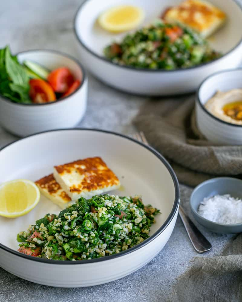 Tabbouleh salad in a whit bowl with two square pieces of pan fried halloumi cheese and half cut lemon