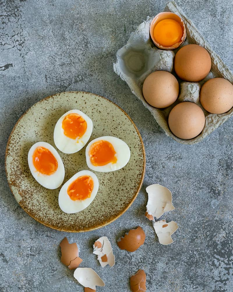 Soft boiled eggs in a ceramic plate showing the texture of the egg yolk. On the side a small tray of whole eggs and few broken egg shells from the peeled boiled eggs to make aioli sauce