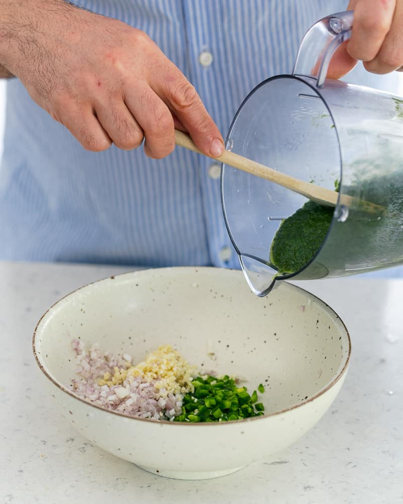 Adding green carrot tops from blender into bowl with other ingredients to make chimichurri sauce