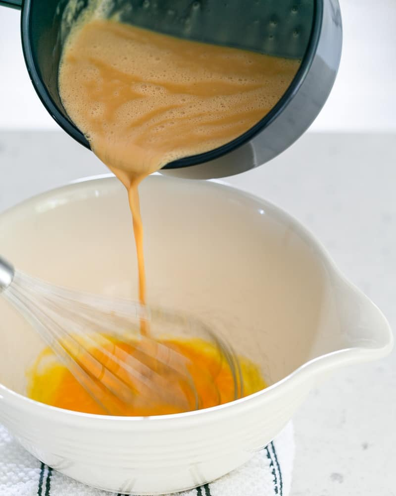 Pour the Caramel and milk and cream mixture over the whisked eggs in the bowl