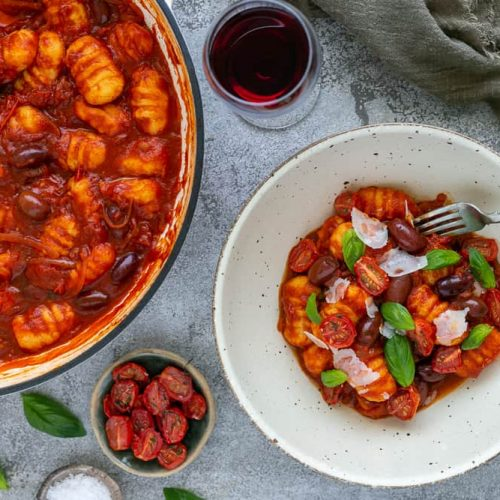 Ricotta Gnocchi's with Tomatoes and olives plated in a bowl with the Gnocchi pan in the background, oven dried tomatoes and shaved parmesan as garnishes with a glass of red wine on the side