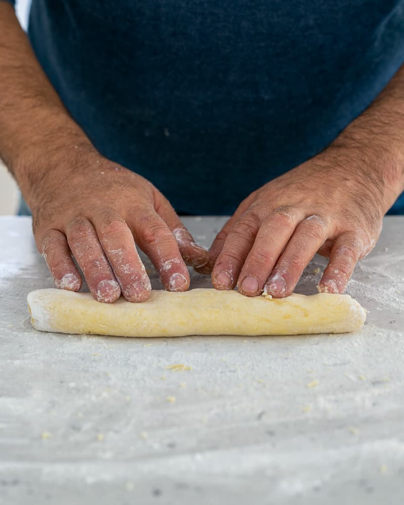 Rolling the dough to make ricotta gnocchi's with tomato and olives