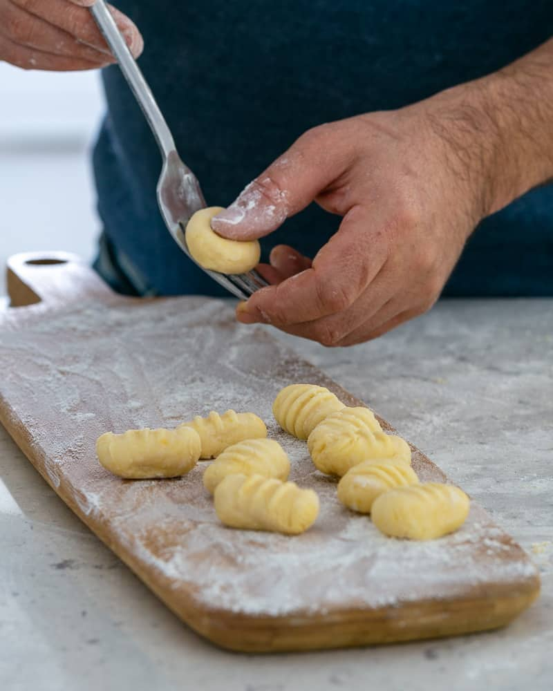 Rolling gnocchi dough balls over a fork to make restaurant style ricotta gnocchi's with tomatoes and olives