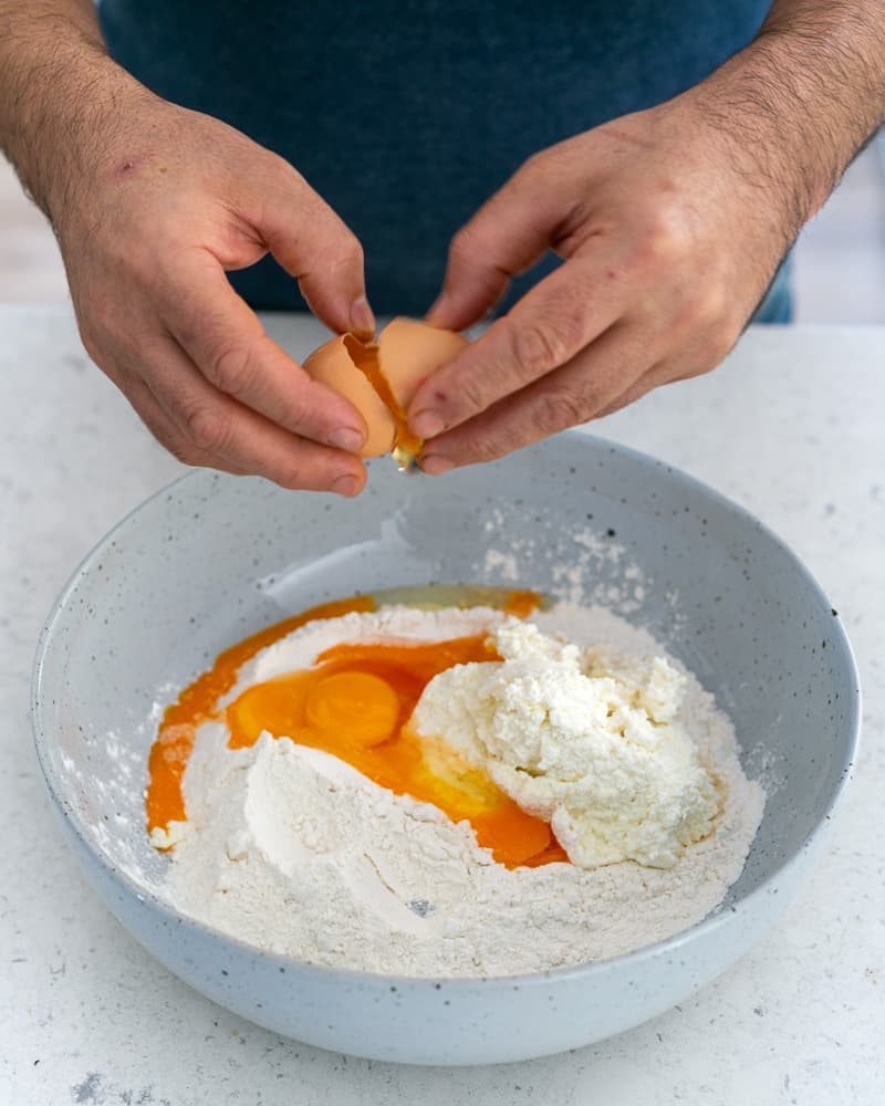 Adding eggs to the Flour and ricotta in a bowl