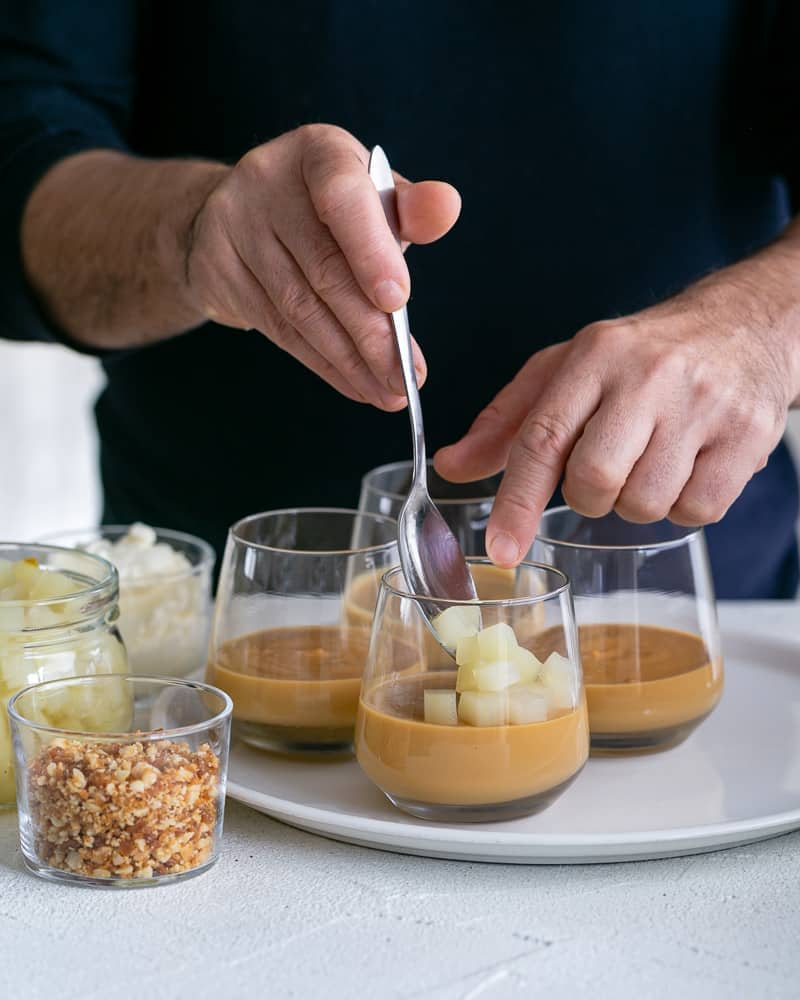Layering the caramel petit pots with poached diced pears