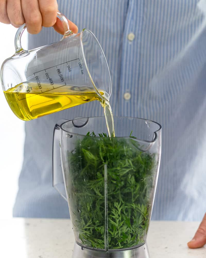 Adding olive oil to carrot top greens in blender to prepare chimichurri