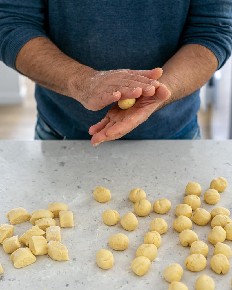 Rolling the dough into balls to make ricotta gnocchi's with tomato and olives
