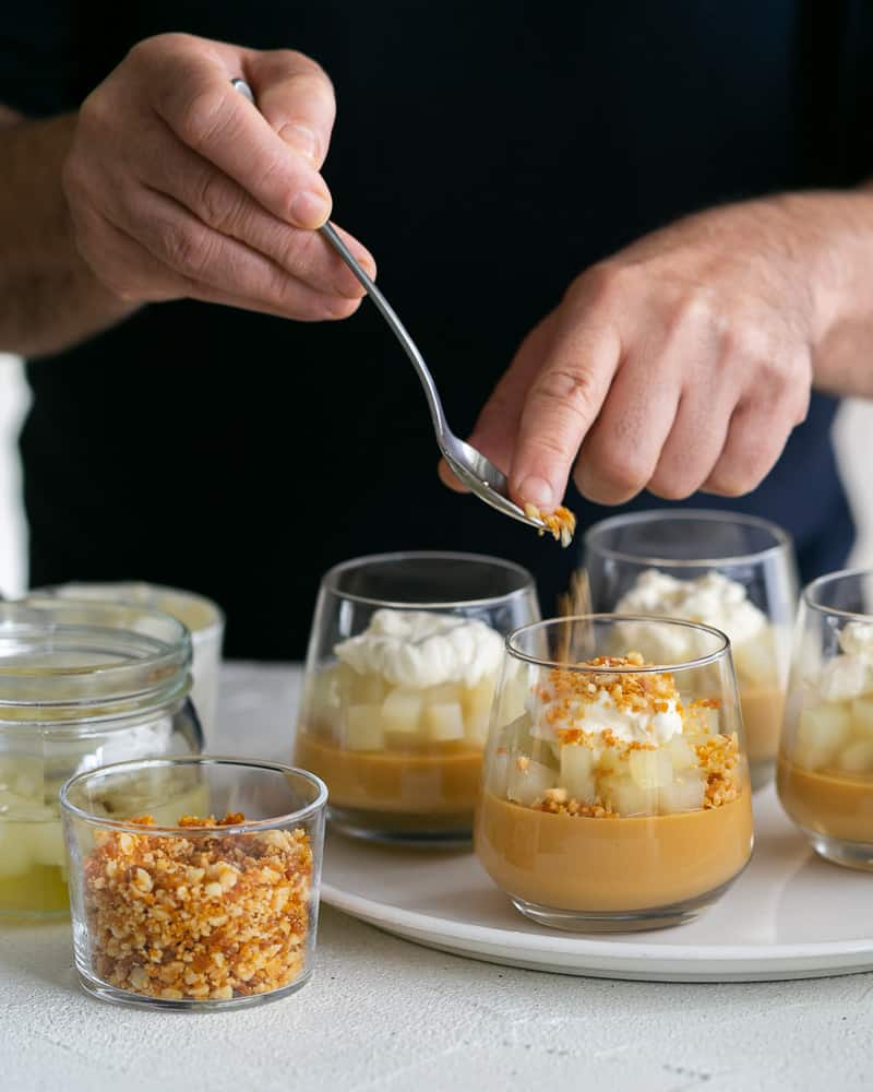 Sprinkle of Macadamia Brittle crumble on top of the whipped cream on caramel petit pots with poached pears