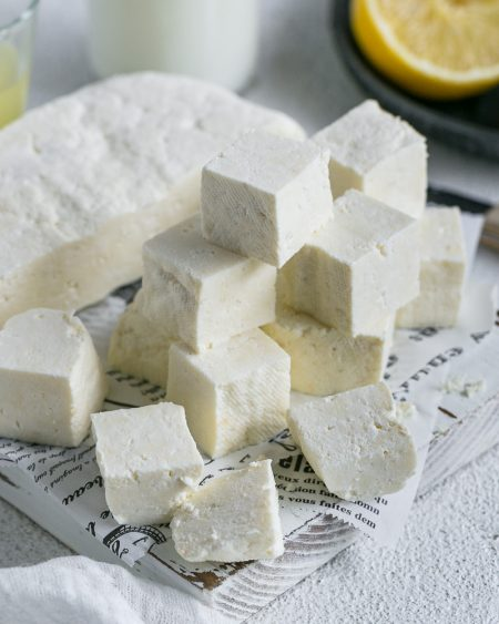 Paneer cut in cubes with half the paneer slab along with lemon juice and milk in background for How to make paneer